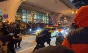 Полиция заламывает людей прямо на проезжей части перед аэропортом.